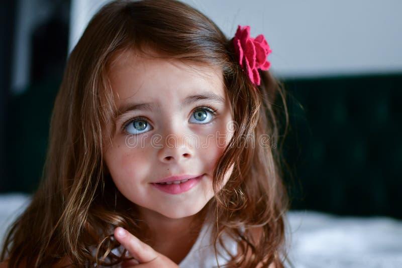 Pouca menina dos sorrisos com uma flor em seu cabelo fotos de stock royalty free