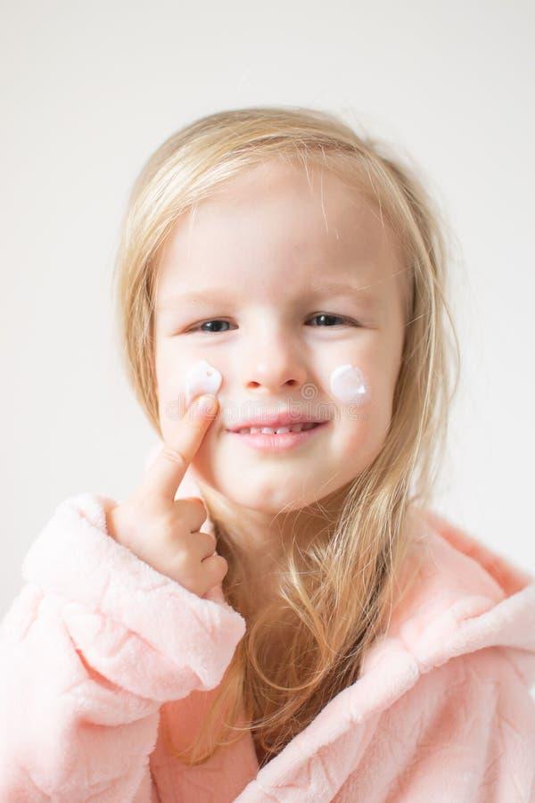 Pouca moça que aplica o creme hidratando em sua cara Conceito dos cuidados com a pele e da beleza fotografia de stock