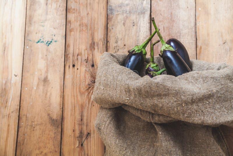Poucas beringelas são vistas no saco em placas de madeira imagem de stock royalty free