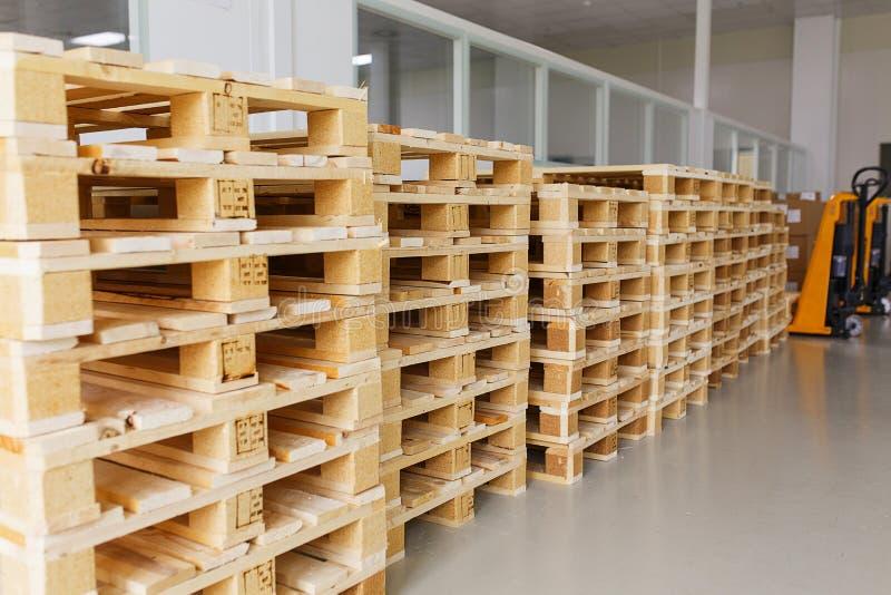 Poucas páletes de madeira vazias para o armazenamento em um armazém vazio fotografia de stock royalty free