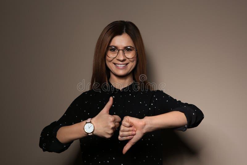 POUCE d'apparence de femme à travers le geste dans la langue des signes sur le fond images stock