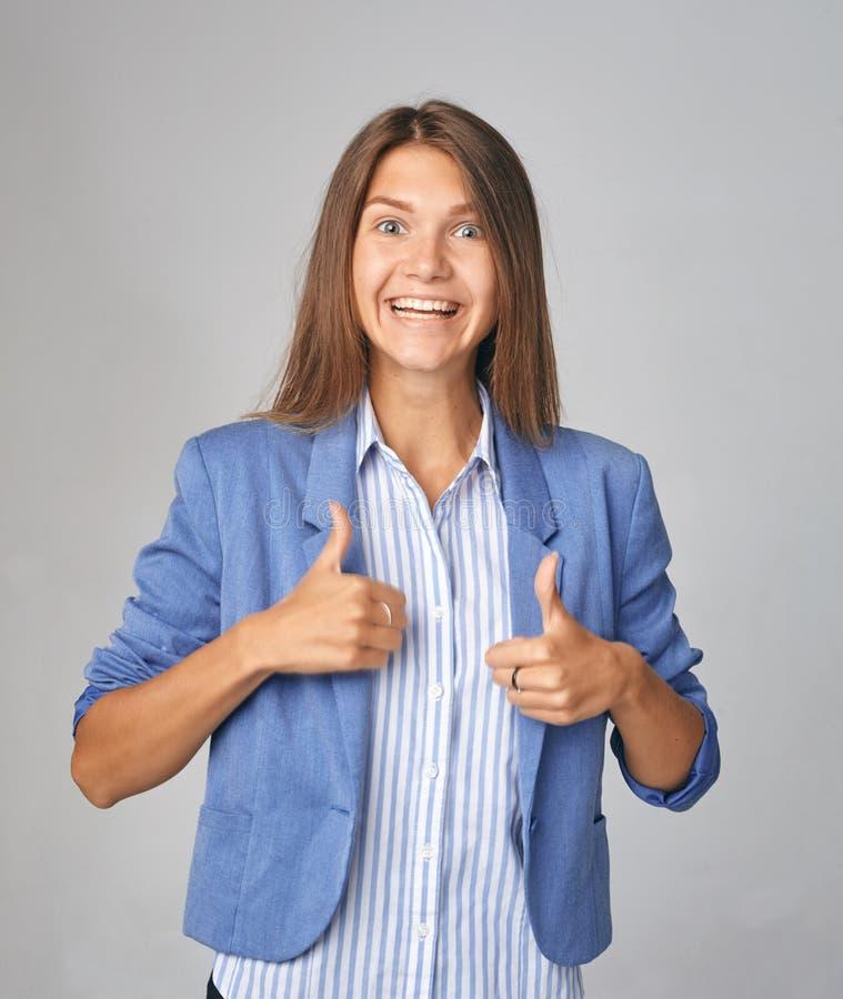 Pouce d'apparence de femme d'affaires au-dessus de fond gris Port dans la veste bleue regarder l'appareil-photo photographie stock libre de droits
