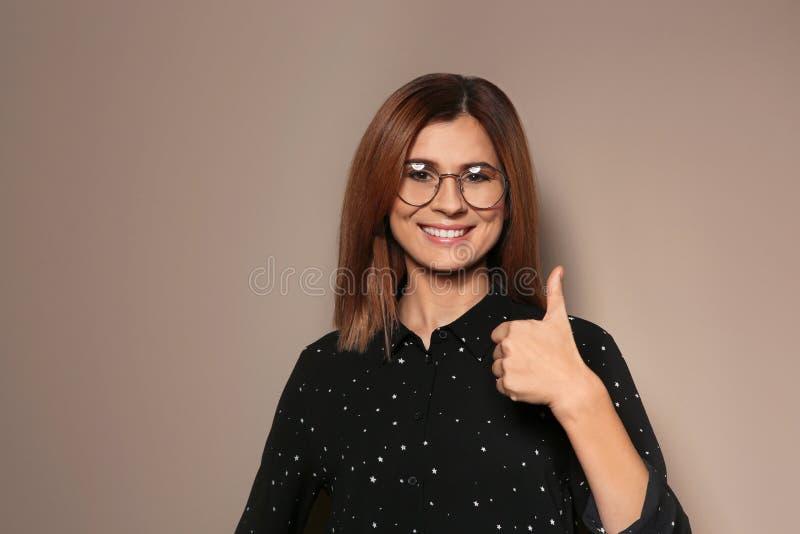 POUCE d'apparence de femme VERS LE HAUT de geste dans la langue des signes sur le fond de couleur photographie stock libre de droits