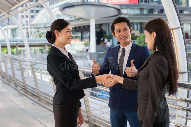 Pouce d'exposition d'homme d'affaires haut et femme des affaires deux se serrant la main pour démontrer leur accord de signer l'a images stock