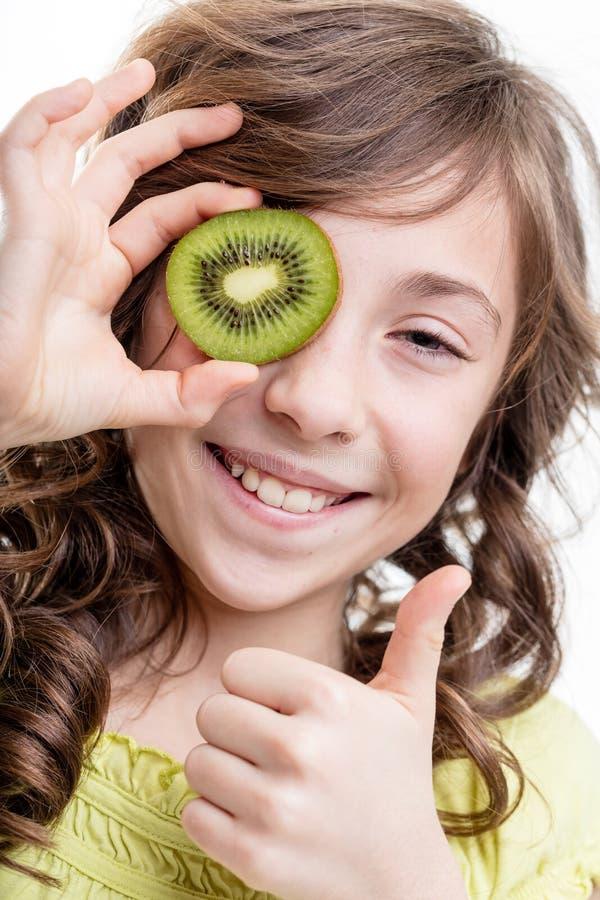 Pouce de fille pour des vitamines de vert de kiwi images stock