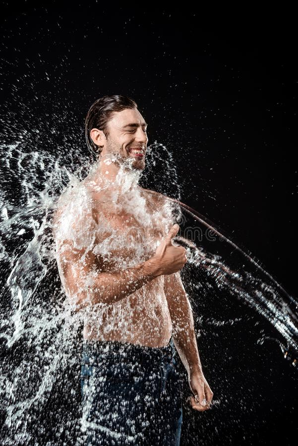 pouce de sourire d'apparence de jeune homme tandis que swilled avec l'éclaboussure de l'eau photo stock