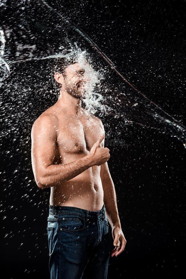 pouce de sourire d'apparence de jeune homme tandis que swilled avec de l'eau photographie stock libre de droits