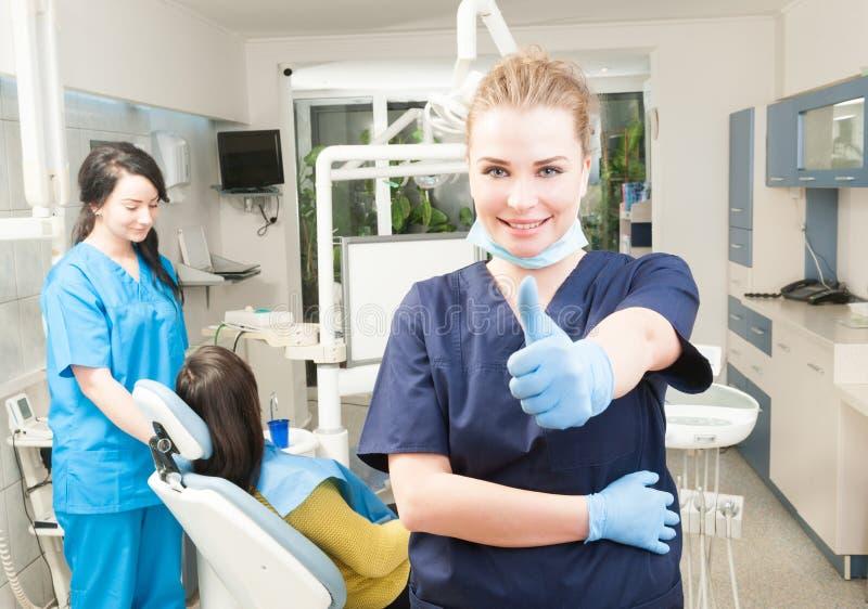 Pouce femelle de sourire sûr de dentiste dans son bureau dentaire photos libres de droits