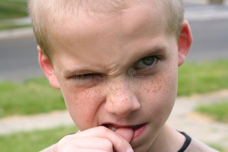 Pouce mordant de garçon photo libre de droits