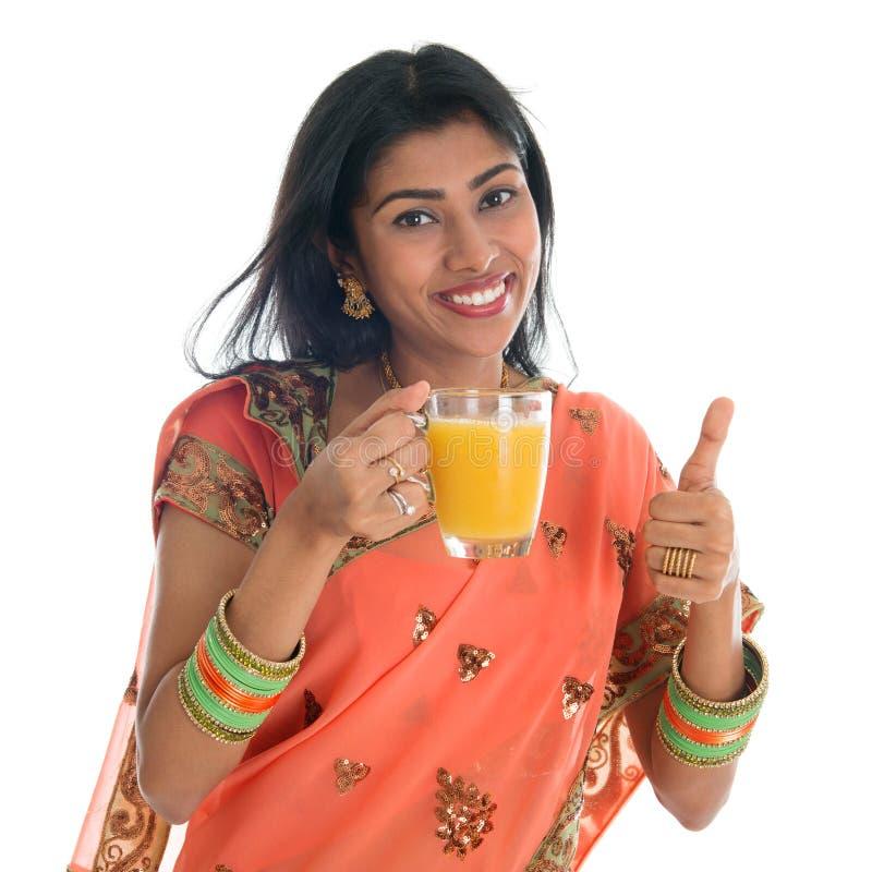 Pouce vers le haut de la femme indienne buvant du jus d'orange photos stock