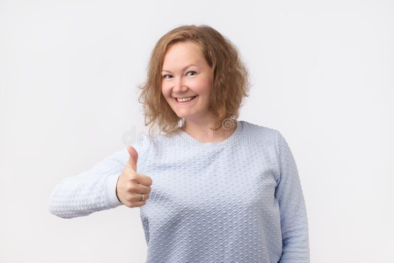 Pouce vers le haut de signe Femme européenne heureuse dans la chemise bleue d'isolement sur le fond gris images stock