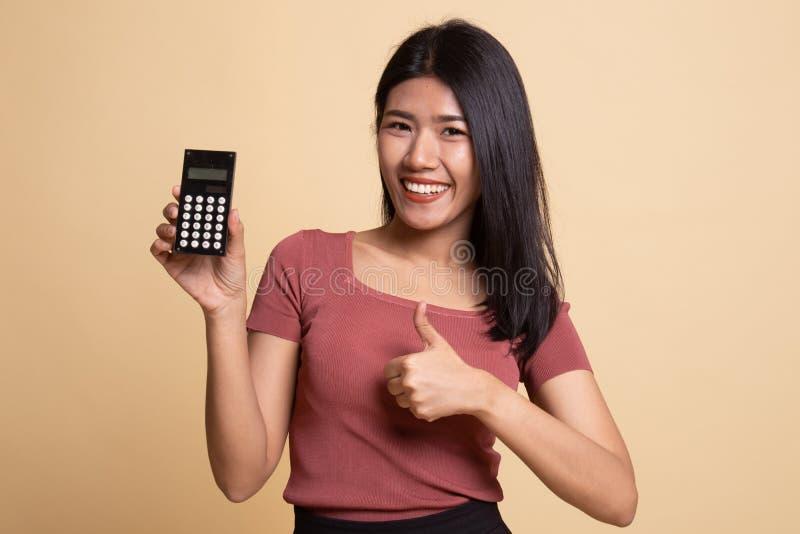 Pouces asiatiques de femme avec la calculatrice photos libres de droits