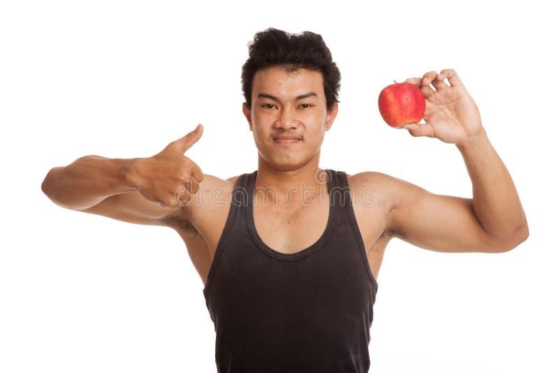 Pouces asiatiques musculaires d'homme avec la pomme rouge photo stock