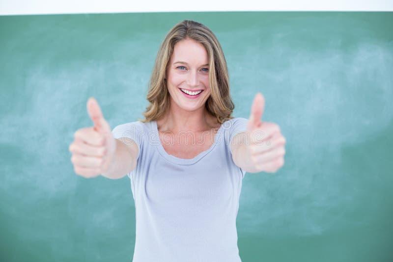 Pouces debout de sourire de professeur devant le tableau noir photo stock