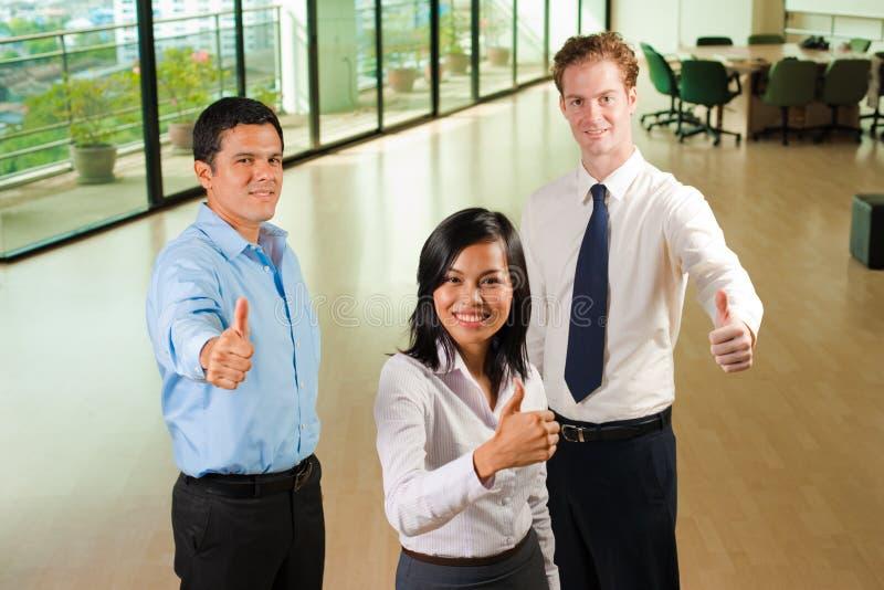 Pouces divers de l'équipe trois d'affaires vers le haut photos stock