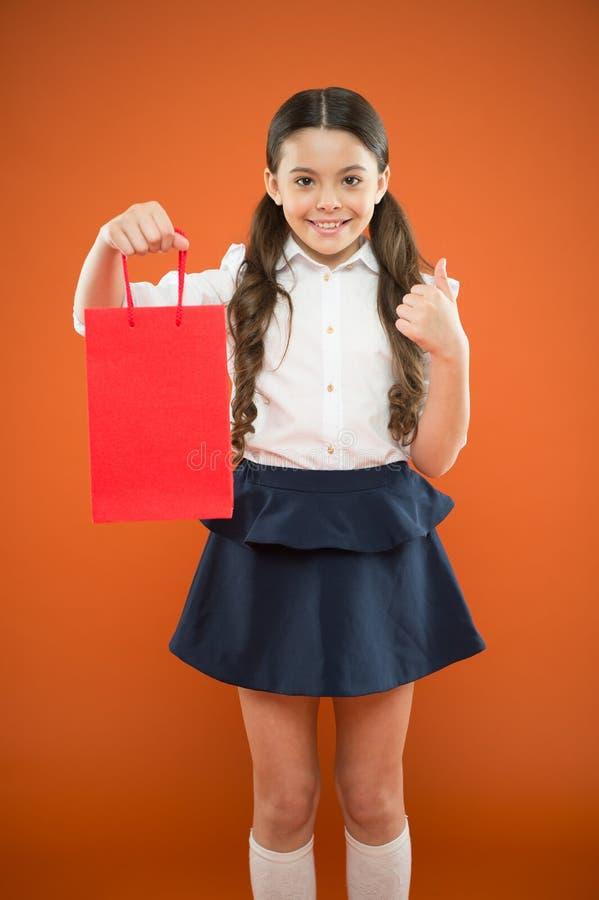Pouces en vente Le petit signe mignon d'ok d'apparence d'enfant d'acheter a acheté à la vente sur le fond orange Petite fille heu photos libres de droits