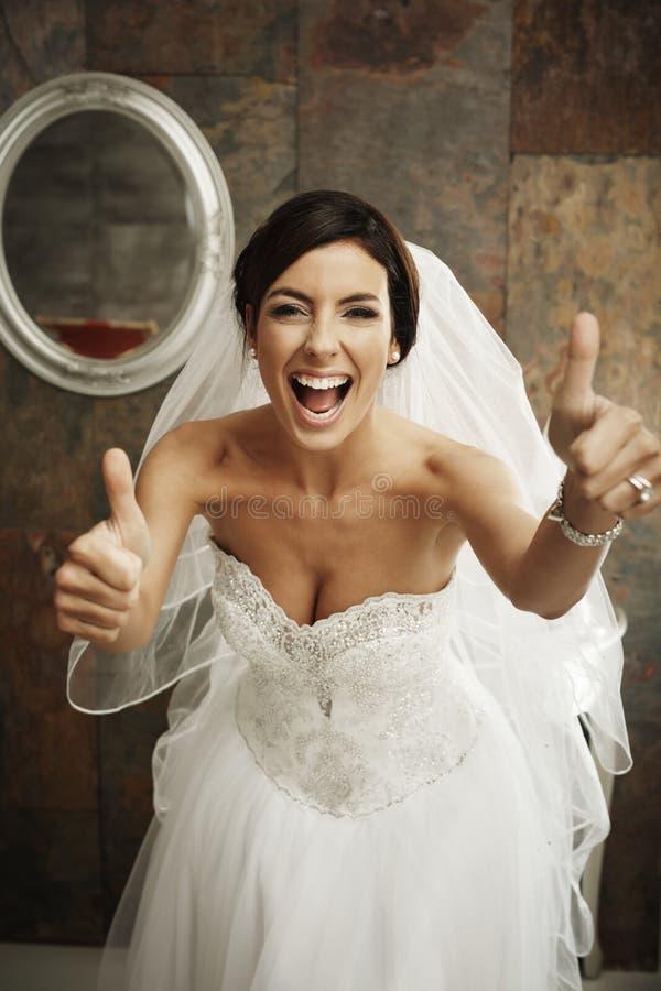Pouces heureux de jeune mariée  photographie stock