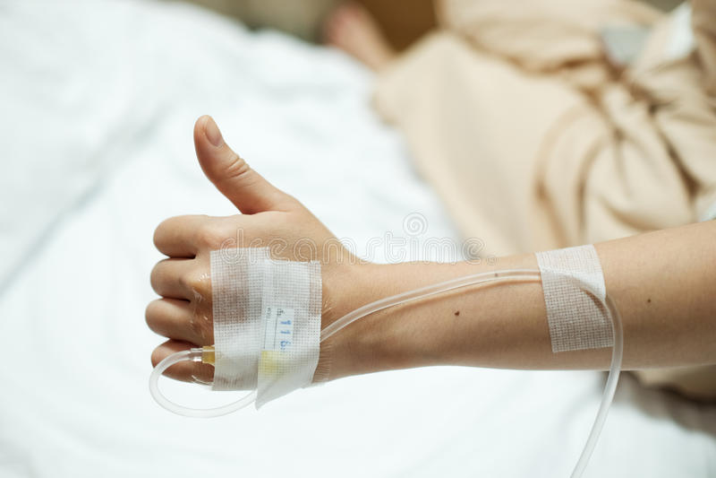 Pouces patients de main tandis qu'injection saline donnée de l'égouttement IV sur le lit d'hôpital photo stock