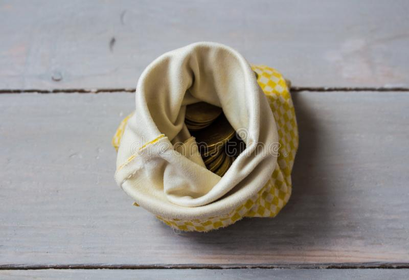 Pouch of gold coins on wooden background stock image