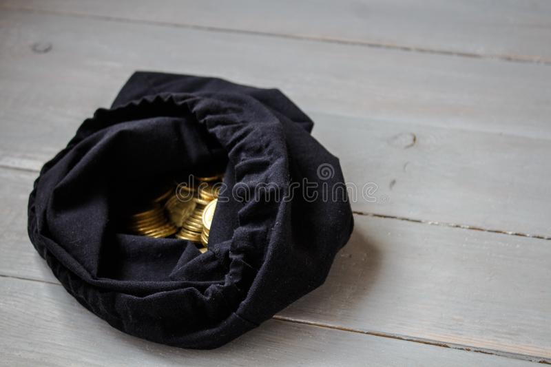 Pouch of gold coins on wooden background stock photography