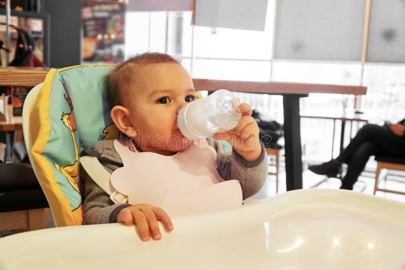 Pouco água potável do bebê da garrafa dentro fotos de stock