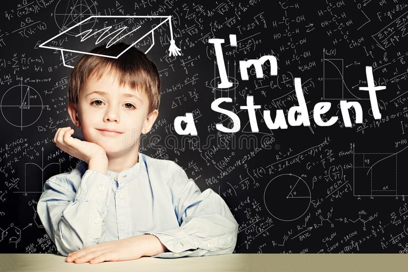 Pouco aluno inteligente do menino no retrato do quadro-negro fotos de stock