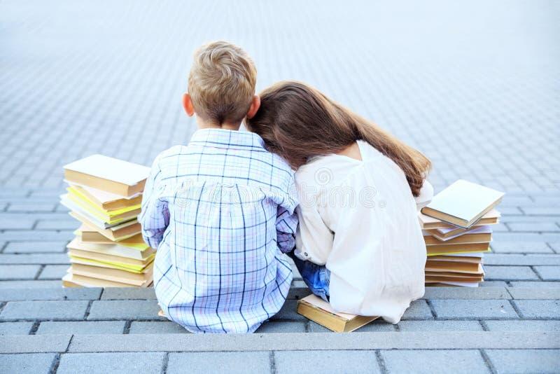 Pouco amigos menino e menina leu livros O conceito é de volta à escola, à educação, à leitura, à amizade e à família foto de stock