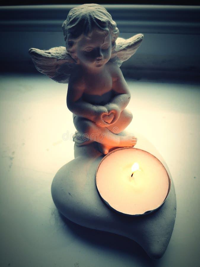 pouco anjo com um coração em suas mãos, castiçal fotos de stock