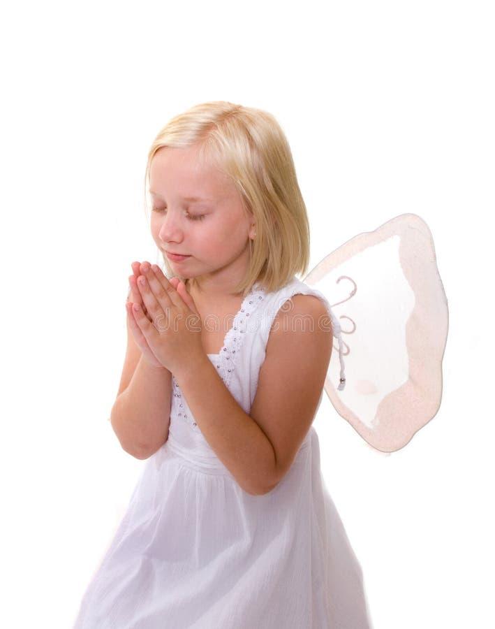 Pouco anjo: Menina que praying, asas desgastando fotos de stock royalty free