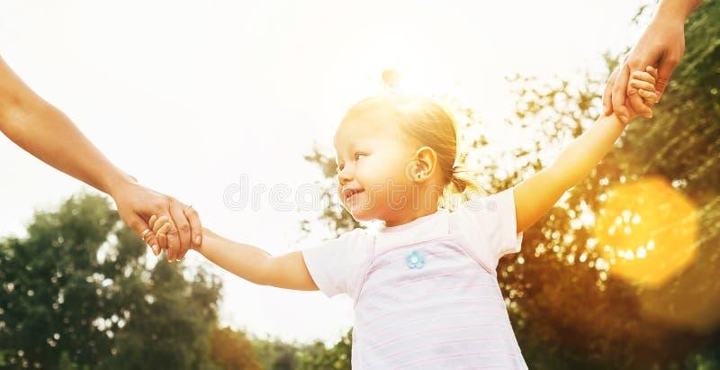 Pouco 2 anos de menina idosa que anda com os pais que guardam sua imagem brilhante do verão das mãos imagem de stock