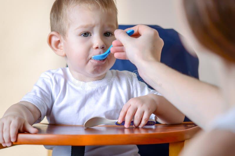 Pouco bebê aprende comer na tabela das crianças na cozinha A mamã alimenta guardar à disposição uma colher do papa de aveia imagens de stock