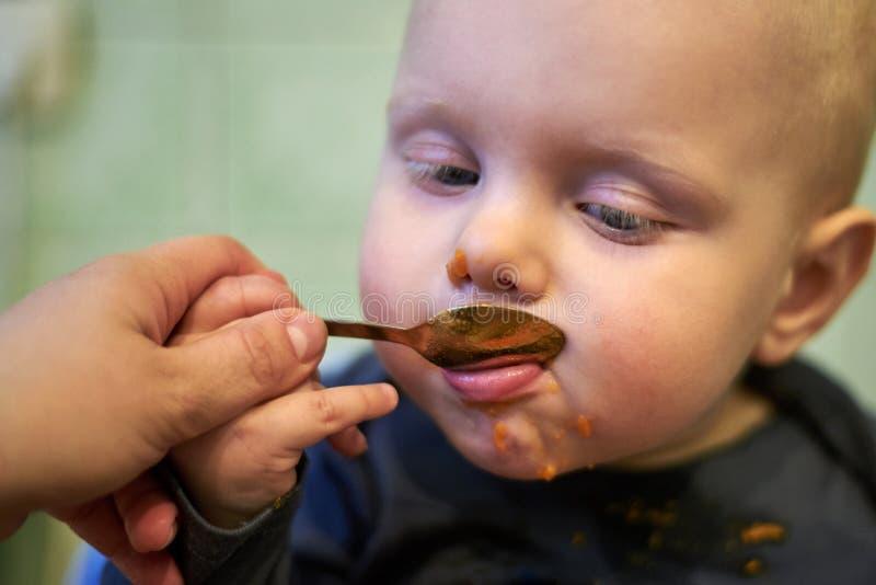 Pouco bebê aprende comer por si próprio com uma colher fotografia de stock royalty free
