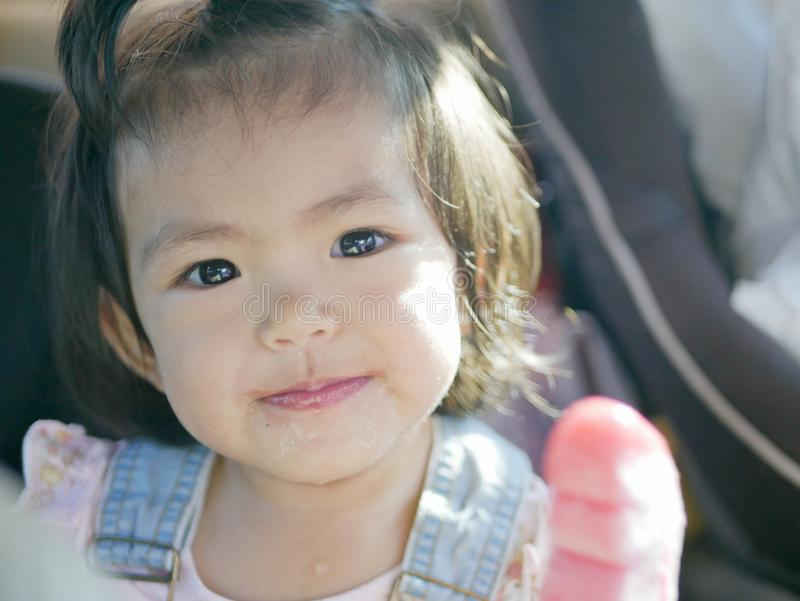 Pouco bebê asiático aprecia comer o gelado em um carro imagem de stock royalty free