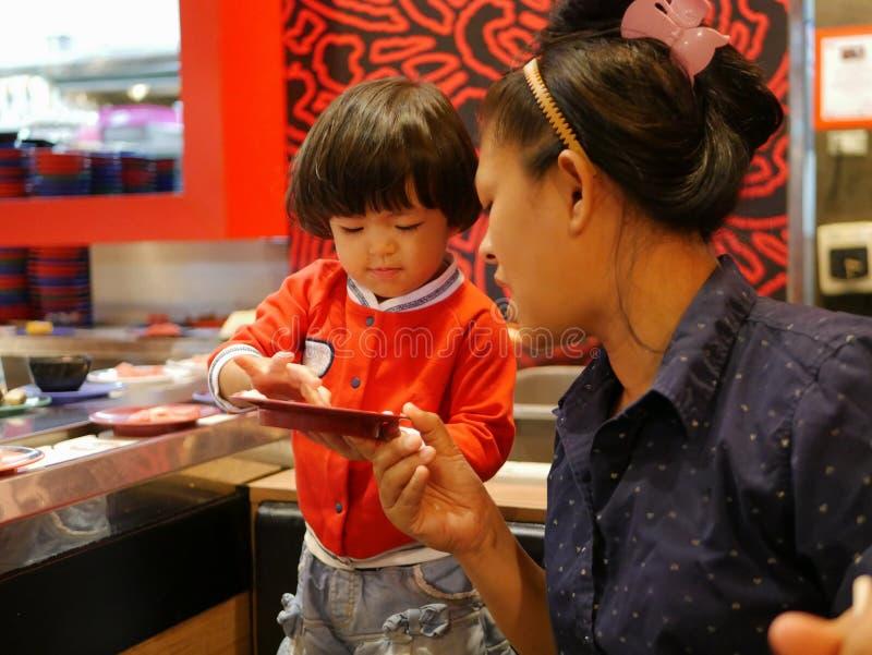 Pouco bebê asiático aprecia escolher ingredientes crus, para sua mãe, para o hotpot cozinhando, servindo em uma correia transport foto de stock royalty free