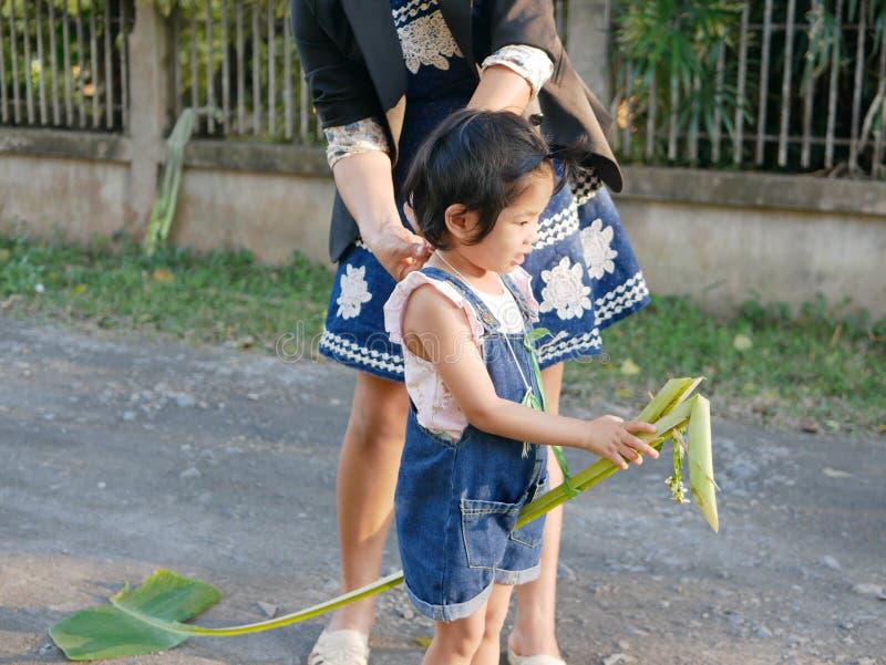 Pouco bebê asiático, com ajuda de sua mãe, preparando-se para jogar o cavalinho de pau do reforço da banana que monta o karn do m foto de stock