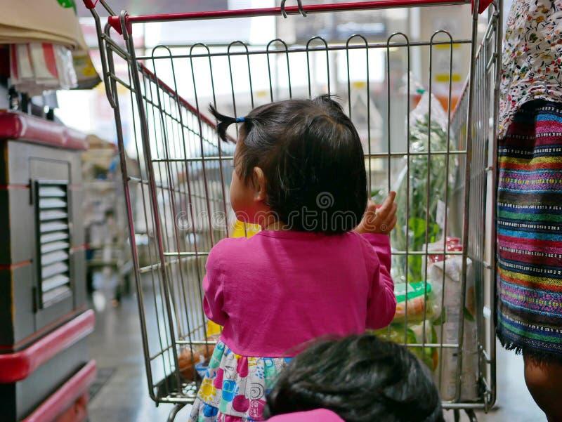 Pouco bebê asiático que ajuda sua mãe a empurrar um carrinho de compras em um supermercado fotografia de stock