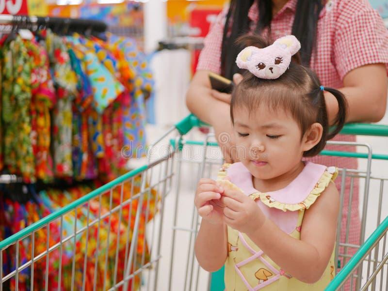 Pouco bebê asiático que come o petisco e que está em um carrinho de compras quando sua mãe fizer uma compra em uma alameda imagens de stock