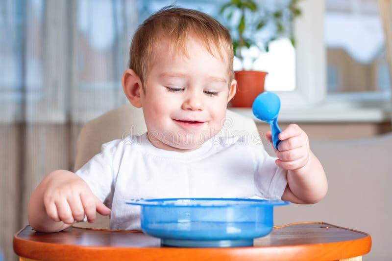 Pouco bebê bonito que aprende comer com uma colher ele mesmo na tabela das crianças na cozinha Comida para bebé saudável imagem de stock royalty free