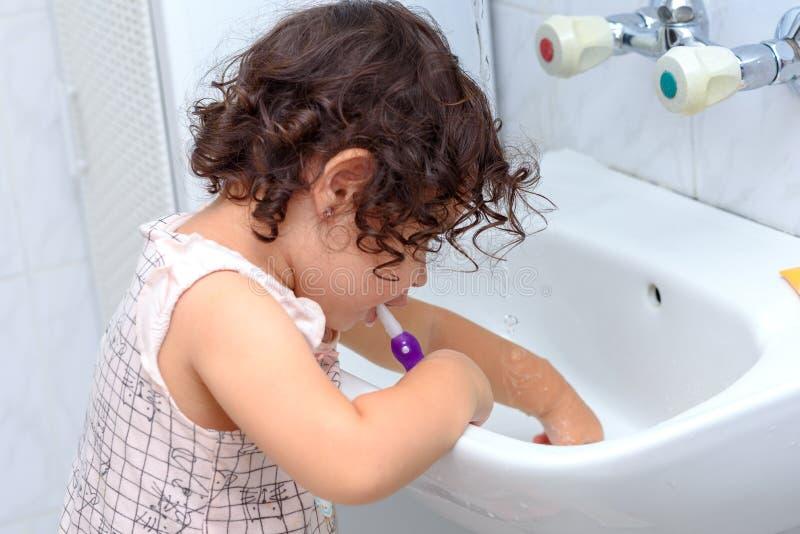 Pouco bebê bonito que limpa seus dentes com a escova de dentes no banheiro foto de stock
