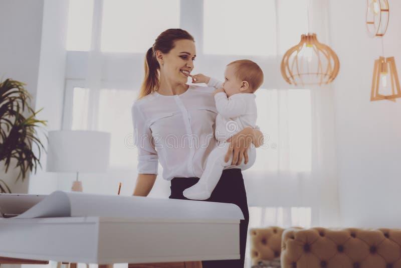 Pouco bebê bonito que toca em seu pai de trabalho industrioso na sala iluminada foto de stock