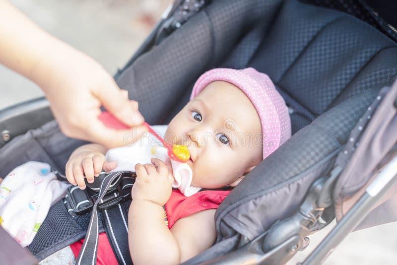 Pouco bebê bonito senta-se em uma cadeira e em comer com colher O bebê de alimentação da mãe que guarda para fora sua mão com uma imagem de stock