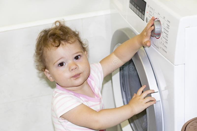 Pouco bebê caucasiano 1 ano gerencie o botão da máquina de lavar foto de stock royalty free