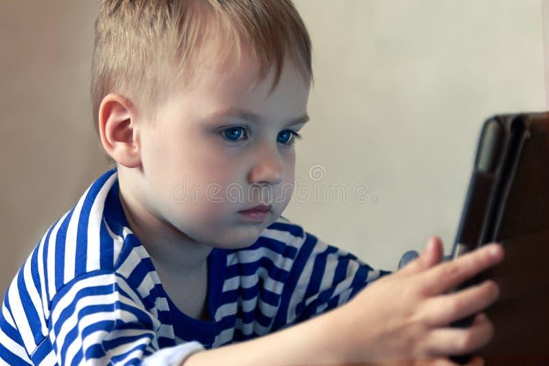 Pouco bebê caucasiano usa uma tabuleta, vendo à tela Despesa do tempo das crianças, automatização dos jovens foto de stock royalty free