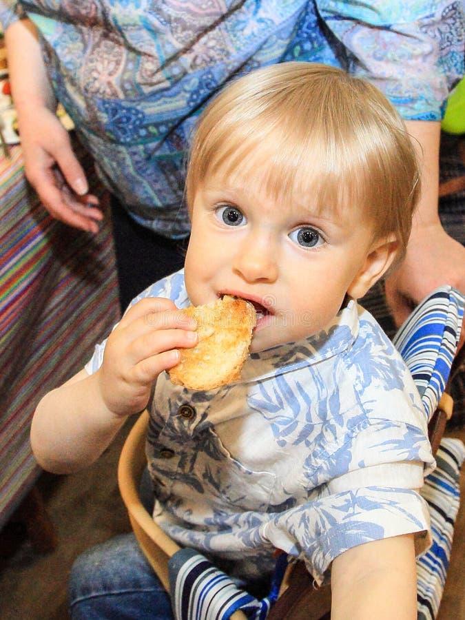Pouco bebê come o pão saboroso foto de stock royalty free