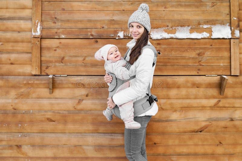 Pouco bebê e sua mãe que babywearing por conseguinte o portador no fundo de madeira do inverno imagem de stock