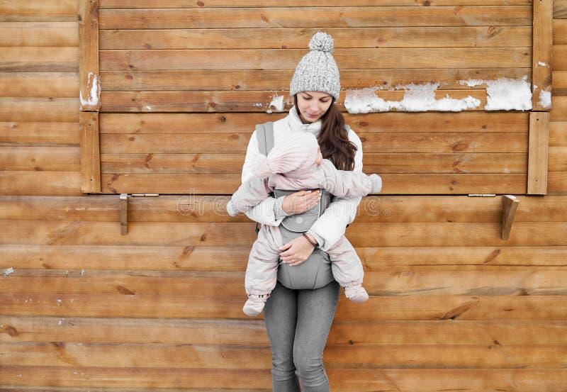 Pouco bebê e sua mãe que babywearing por conseguinte o portador no fundo de madeira do inverno fotos de stock royalty free