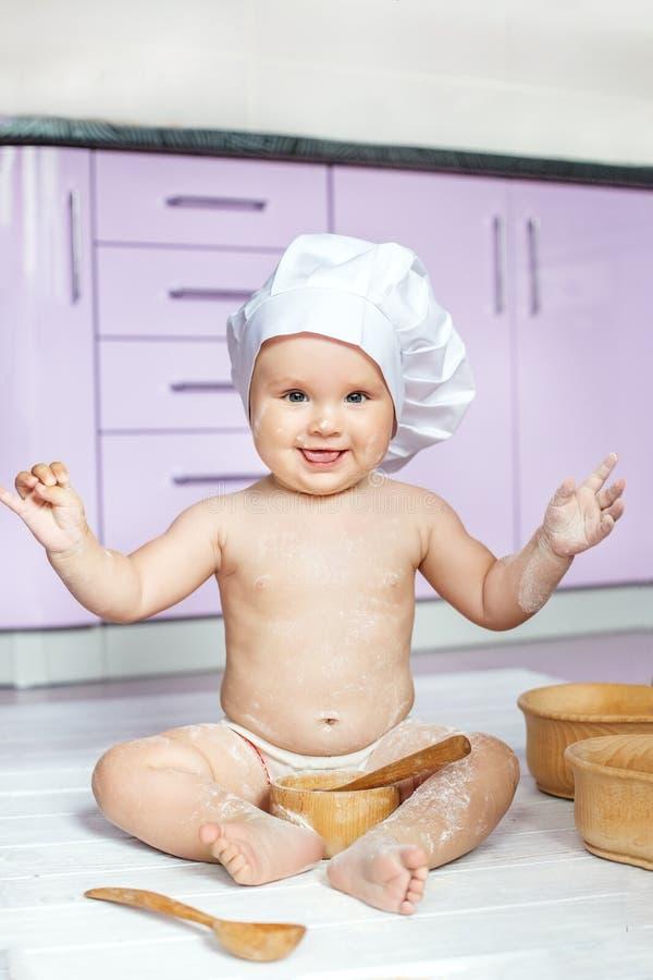 Pouco bebê está jogando na cozinha cozinheiro O conceito do chil imagem de stock
