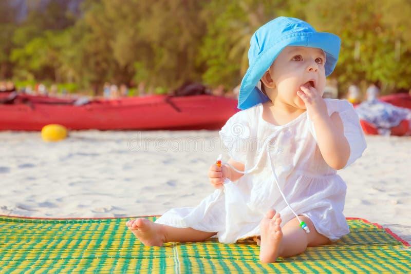 Pouco bebê 8 meses está sentando-se no Sandy Beach no chapéu azul e no vestido branco É imprimida do mar imagens de stock royalty free