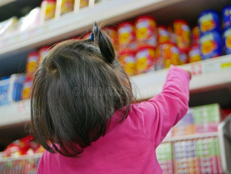 Pouco bebê que aponta em petiscos/doces coloridos nas prateleiras em um supermercado, querendo seus pais comprar algum para ela imagens de stock royalty free