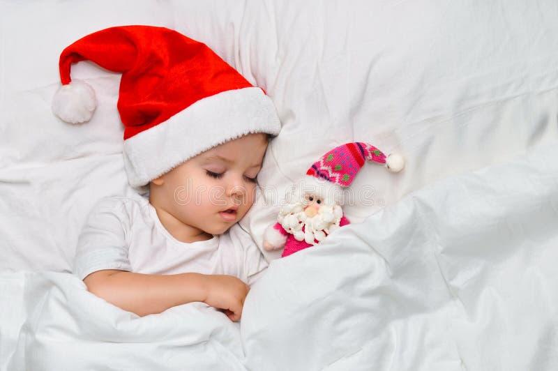 Pouco bebê que dorme no linho branco no chapéu de Santa com seu brinquedo Santa Claus imagens de stock